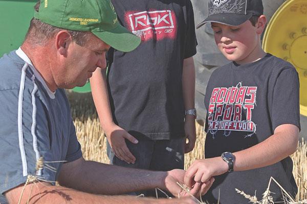 Farmers teaching young men in prairie